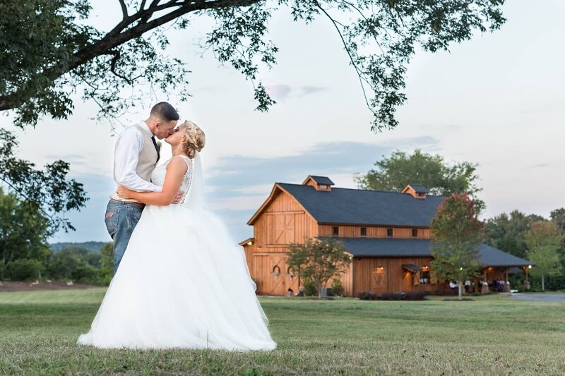 bride and groom kissing outside on lawn in front of windy hill wedding and event barnm
