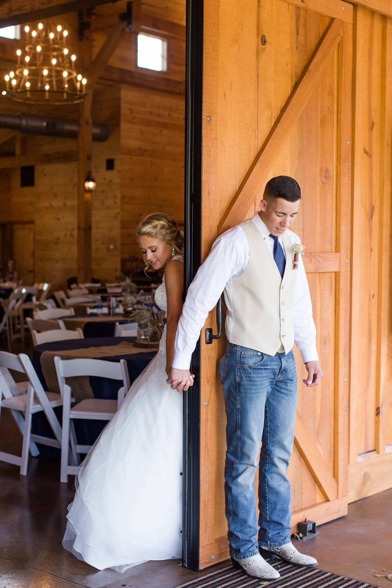 bride and groom holding hands around door inside windy hill wedding and event barn